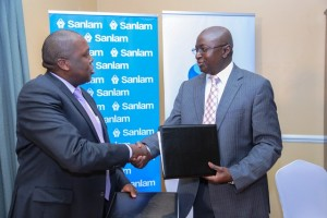 Group Chief Executive Officer Sanlam Kenya, Mugo Kibati (left) and Standard Chartered Bank Chief Executive Officer, Lamin Manjang (right) exchange a handshake sealing the partnership deal to provide general insurance through the bank's wide spread distribution channels, at the Stanley Hotel, Nairobi.